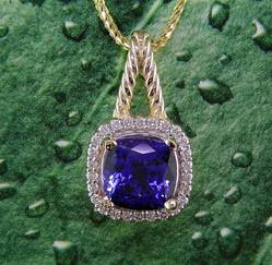 14K yellow gold twist pendant with 3.79 carat cushion tanzanite and .25 ct. of diamond.