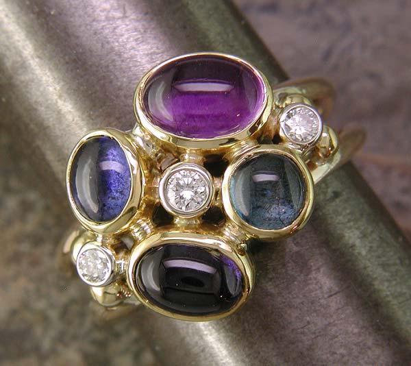 Split shank ring with bezel-set diamonds, amethyst, iolite, topaz, and tanzanite.