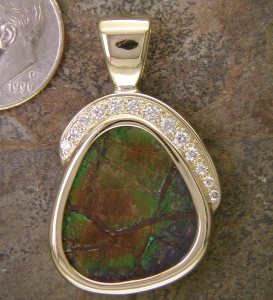 14K gold and diamond surrounding solid ammolite. A fossil gemstone found only in Canada.
