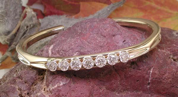 14K gold cuff with bezel-set diamonds.