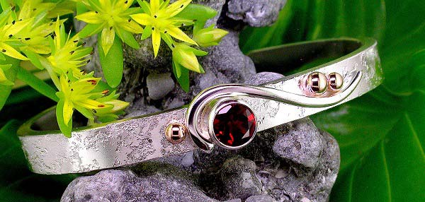 textured sterling silver cuff style bracelet with garnet and 14K yellow gold bead accents.