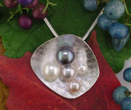 Patterned sterling silver sheet with natural and dyed cultured pearls.