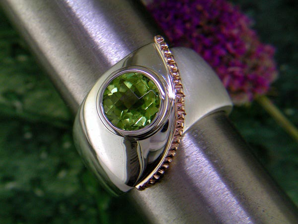 Brushed and polished sterling silver ring with peridot and 14K rose gold accent.