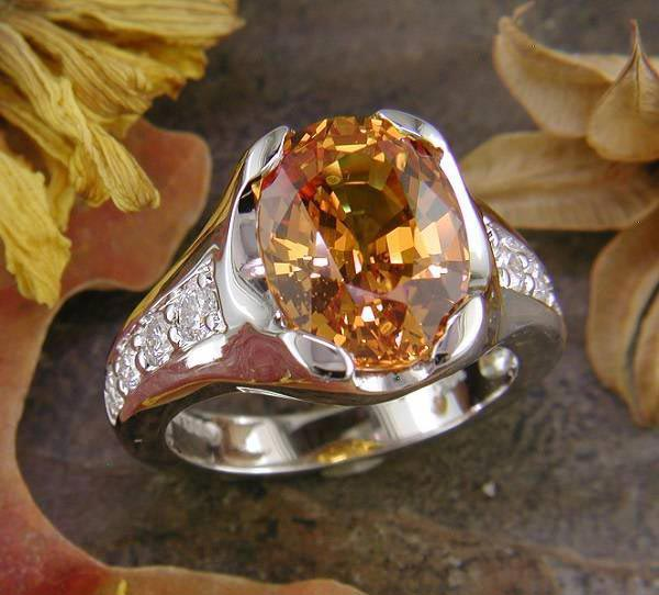 14K white gold with 6.96 ct. golden orange sapphire and .44 carats of diamond accent.