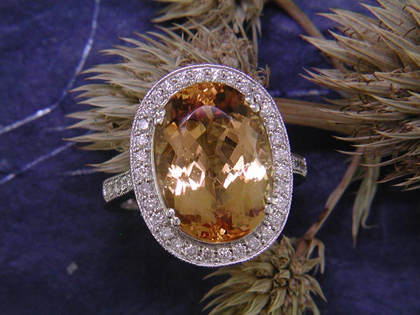 10.80 carat precious topaz accented by .51 carat of round diamond side stones.