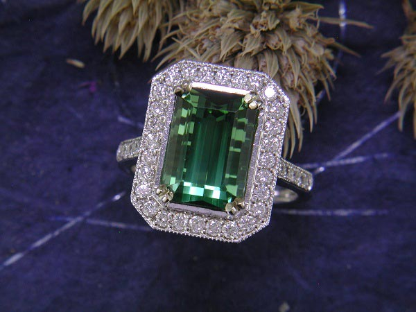 5.18 carat green tourmaline surrounded by .64 carat of round diamond accents.