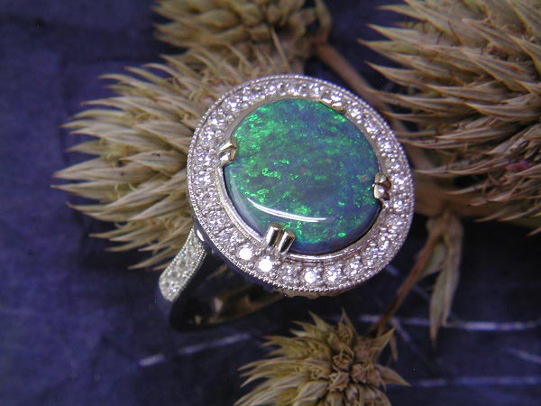 Amazing 3.57 carat r'oval solid black opal surrounded by .62 carat weight of round diamond.