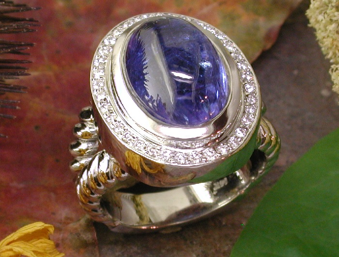 A custom made 14K white gold ring around a cabochon Tanzanite surrounded with a rim of round bead-set diamonds.