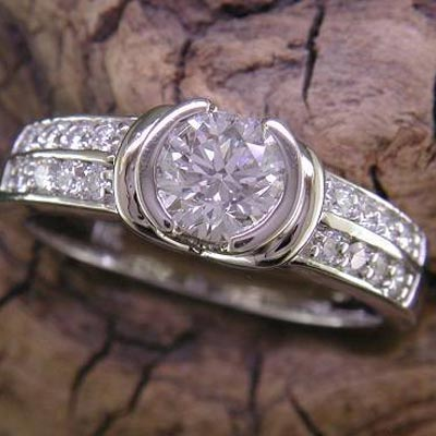 Semi-bezel set round diamond with diamond double row accents down the shoulders.