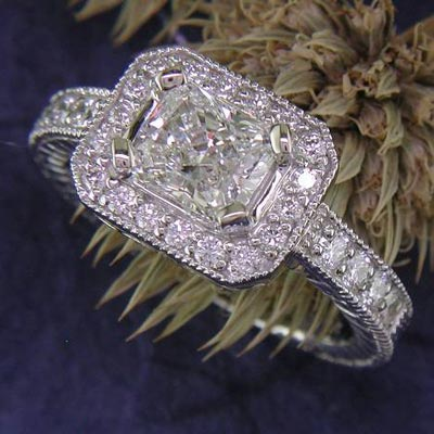 14K white gold East/West set radiant cut diamond in a halo.