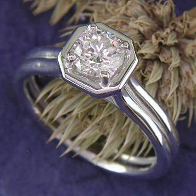 An unorthodox octagonal-framed solitaire containing a round diamond center stone.