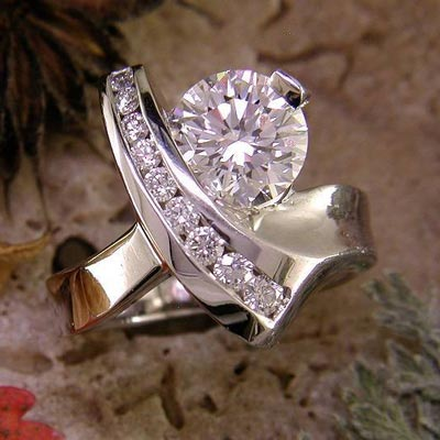 14K white gold ring with round diamond and channel-set diamond accents.