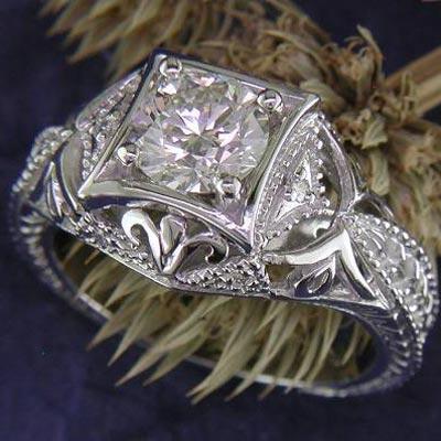 14K white gold engagement ring with illusion-set round center stone.